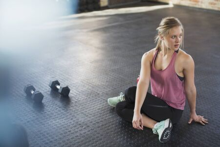 Young woman stretching, twisting in gym next to dumbbells