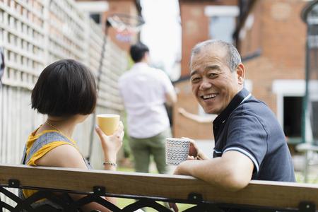 Portrait happy senior man drinking tea with family in back yard