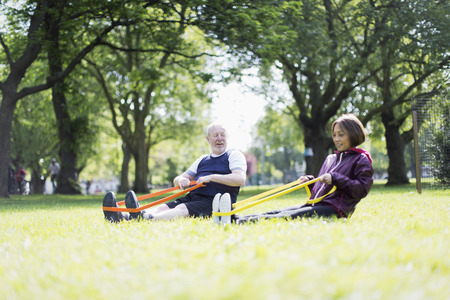 Active senior couple exercising, using resistance bands in park LANG_EVOIMAGES