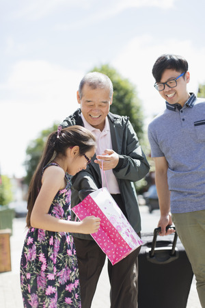Grandfather visiting family, surprising granddaughter with gift LANG_EVOIMAGES