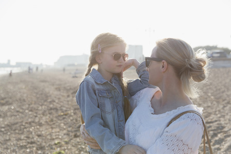 Mother and daughter wearing sunglasses on sunny beach