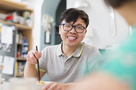 Happy man eating noodles with chopsticks LANG_EVOIMAGES
