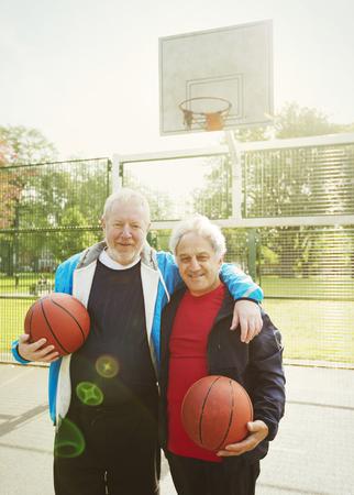 Portrait confident active senior men friends playing basketball in sunny park LANG_EVOIMAGES