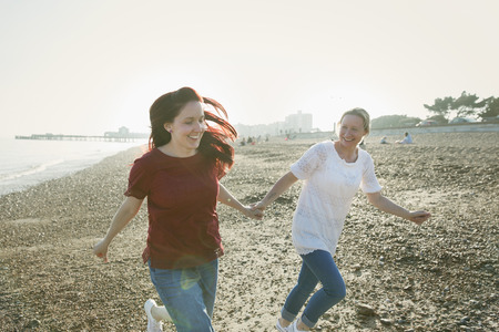 Playful, affectionate lesbian couple holding hands and running on sunny beach