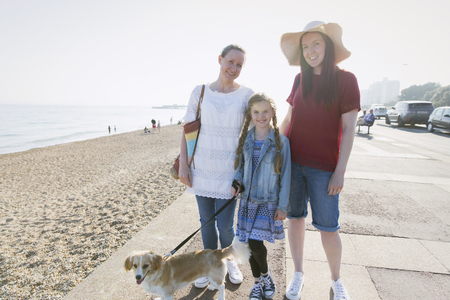 Portrait smiling lesbian couple with daughter and dog on sunny beach boardwalk LANG_EVOIMAGES