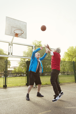Active senior men friends playing basketball in park