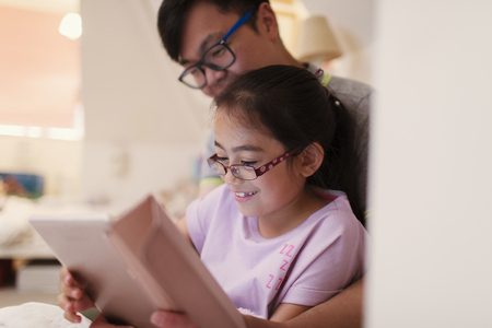 Father and daughter using digital tablet