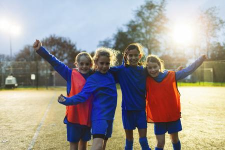 Portrait confident girls soccer team cheering on field