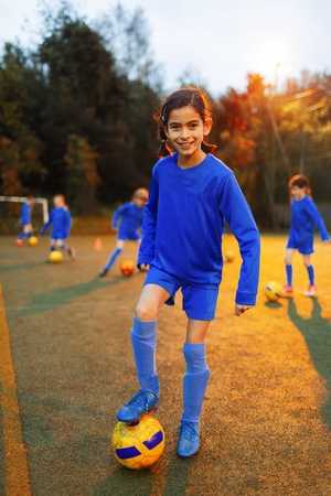 Portrait confident girl practicing soccer on field LANG_EVOIMAGES