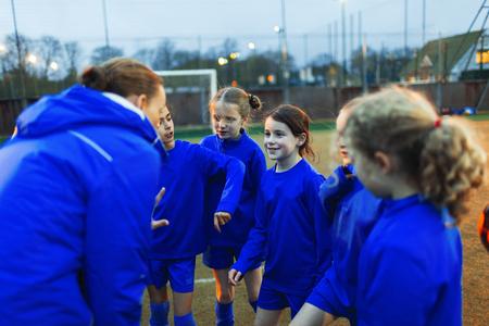 Girls soccer team listening to coach in huddle LANG_EVOIMAGES