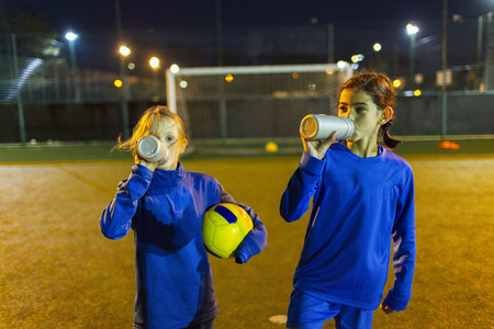Girl soccer players taking a break, drinking water on field at night