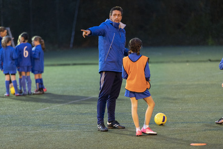 Soccer coach guiding girl soccer players practicing on field at night LANG_EVOIMAGES