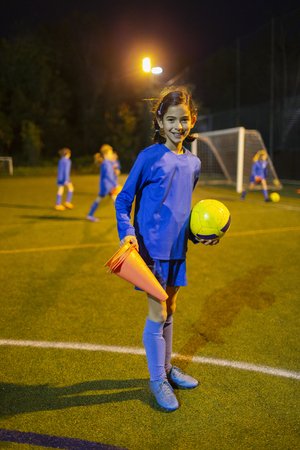 Portrait confident girl soccer player on field at night LANG_EVOIMAGES