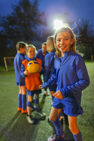 Portrait smiling, confident girl soccer player practicing with team on field at night