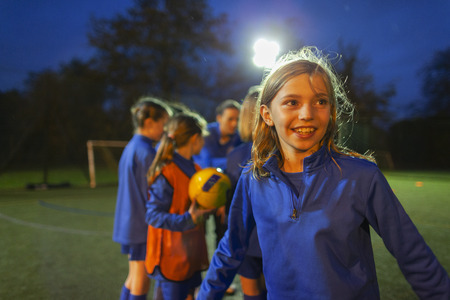 Smiling girl playing soccer on field at night