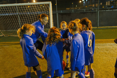 Soccer coach and girls soccer team in huddle on field at night