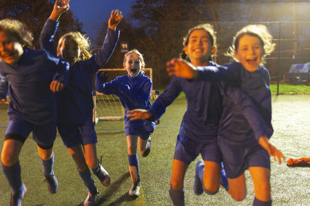 Enthusiastic girls soccer team running and celebrating on field at night