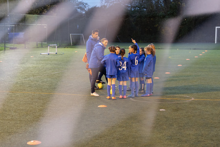 Soccer coaches and girl soccer team talking on field LANG_EVOIMAGES