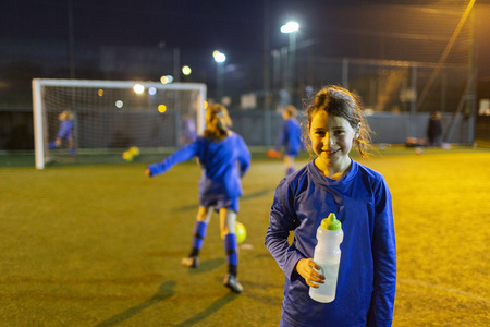 Portrait smiling girl soccer player drinking water on field at night LANG_EVOIMAGES