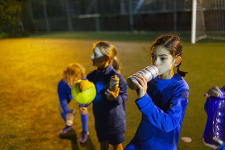 Girl soccer player taking a break, drinking water on field at night