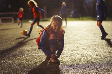 Portrait smiling girl soccer player tying shoe on field at night