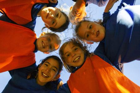 Portrait girls soccer team in huddle