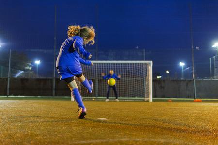 Girl soccer player kicking the ball toward goal LANG_EVOIMAGES