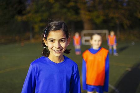 Portrait confident girl playing soccer LANG_EVOIMAGES