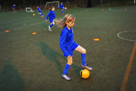 Girl practicing soccer drill on field at night