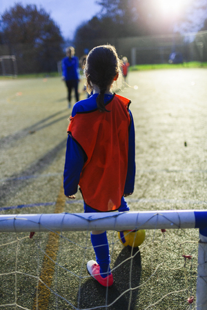 Girl playing soccer on field at night LANG_EVOIMAGES