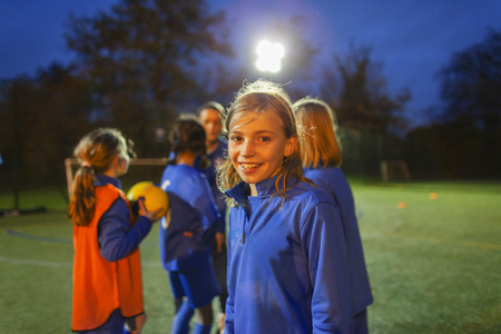 Portrait smiling, confident girl soccer player on field at night