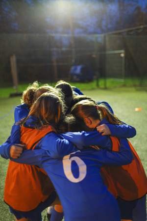 Girls soccer team in huddle on field at night LANG_EVOIMAGES