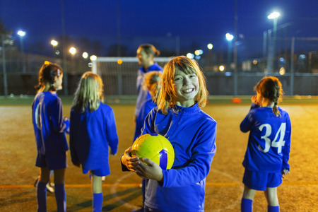 Portrait smiling, enthusiastic girl enjoying soccer practice on field at night