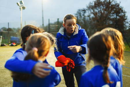 Girls soccer team listening to coach on field at night LANG_EVOIMAGES