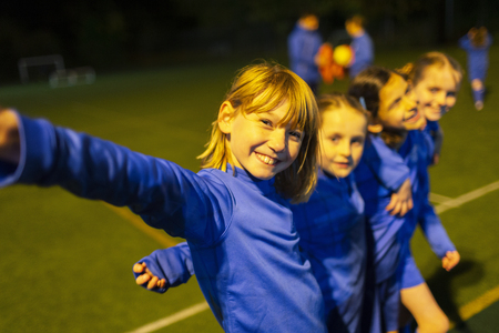 Portrait smiling, confident girls soccer team on field at night