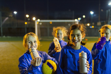 Portrait smiling girls soccer team taking a break from practice, drinking water on field at night LANG_EVOIMAGES