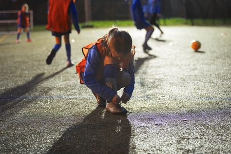 Girl soccer player tying shoe on field at night