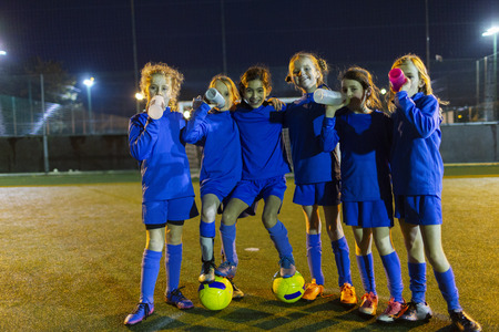 Portrait confident girls soccer team drinking water on field at night LANG_EVOIMAGES