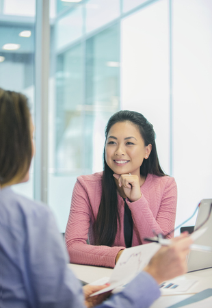 Smiling, attentive businesswoman listening to colleague in meeting