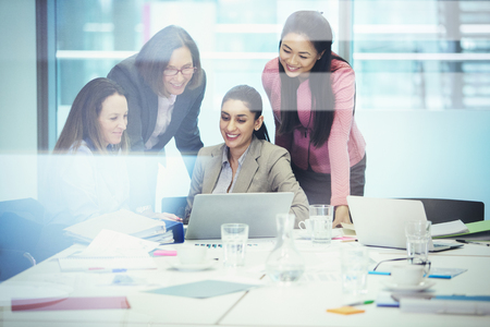 Businesswomen using laptop in conference room meeting LANG_EVOIMAGES