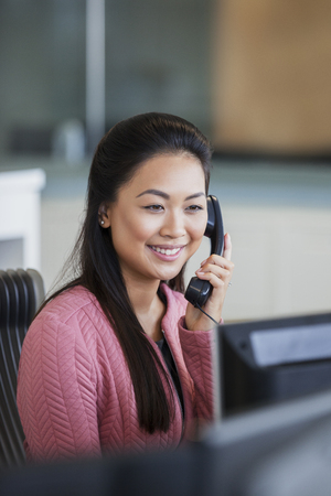Smiling businesswoman talking on telephone in office LANG_EVOIMAGES