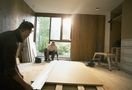 Construction workers measuring wood board in house LANG_EVOIMAGES