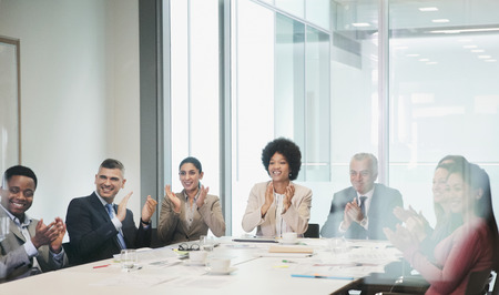 Happy, supportive business people clapping in conference room meeting