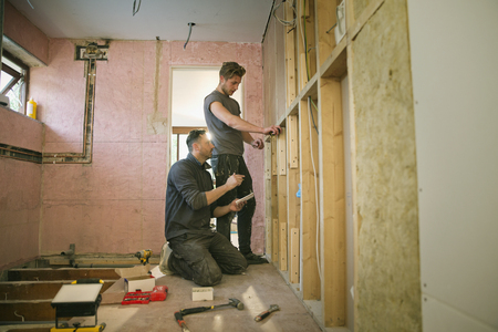 Construction workers framing inside of house LANG_EVOIMAGES