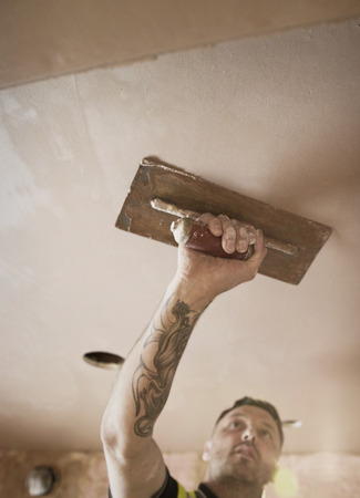 Construction worker with tattoo plastering ceiling LANG_EVOIMAGES