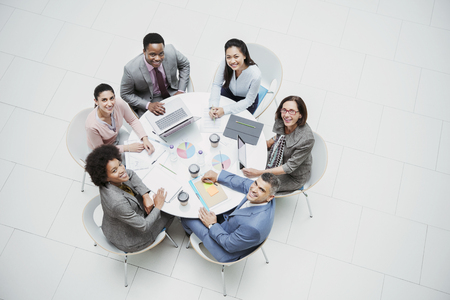 High angle portrait smiling, confident business people meeting at round table