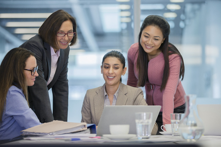 Smiling businesswomen using laptop in conference room meeting