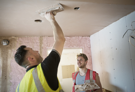 Construction workers plastering ceiling