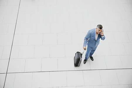 High angle businessman with suitcase talking on cell phone LANG_EVOIMAGES
