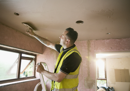 Construction worker plastering ceiling in house